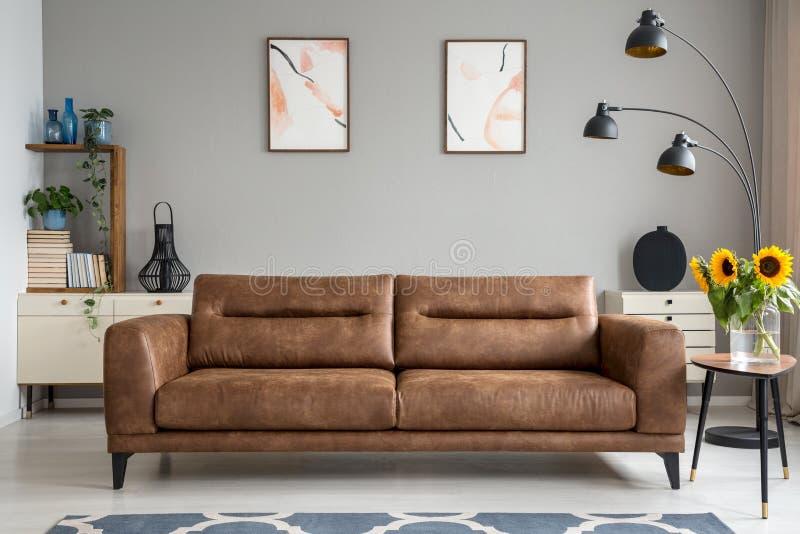 Piska soffan bredvid tabellen med solrosor i grå vardagsruminre med affischer Verkligt foto arkivbilder