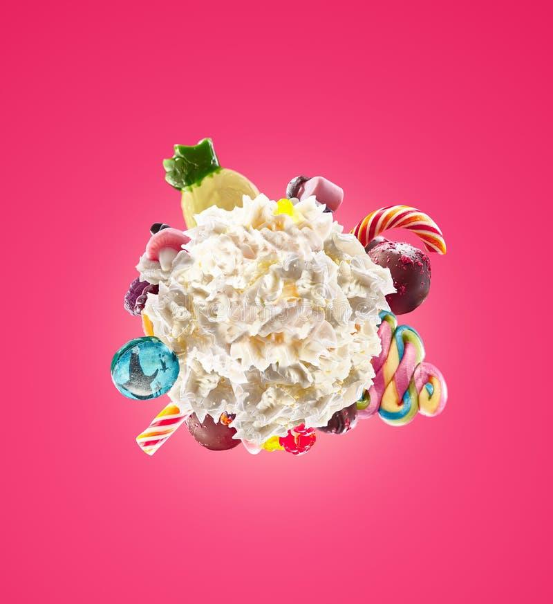 Piskad rundakräm med kulöra isolerade sötsaker, gelé och godisar Sött livbegrepp Piskad söt efterrätt - mjölka arkivbilder