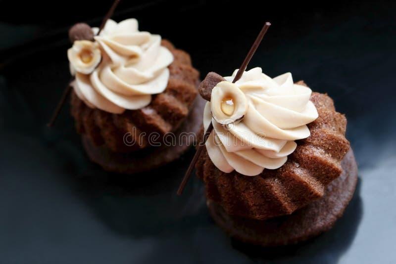Piskade moderna muffin för choklad med hasselnötter ganache som glaserar på svart bakgrund royaltyfria bilder