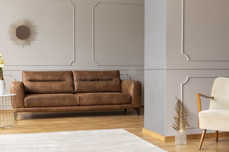 Piskar den plana inre för öppet utrymme med den bruna soffan som gjuter på väggar, vit matta och den guld- dekoren royaltyfri fotografi