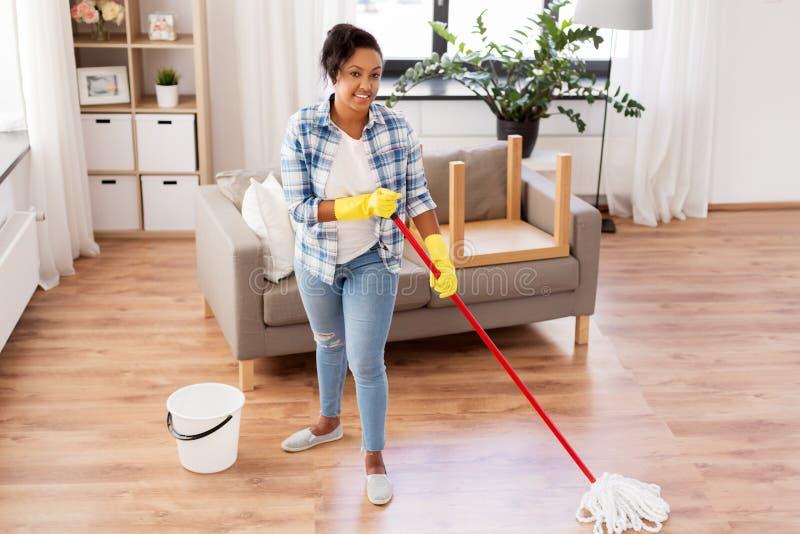 Piso africano de la limpieza de la mujer o del ama de casa en casa foto de archivo libre de regalías