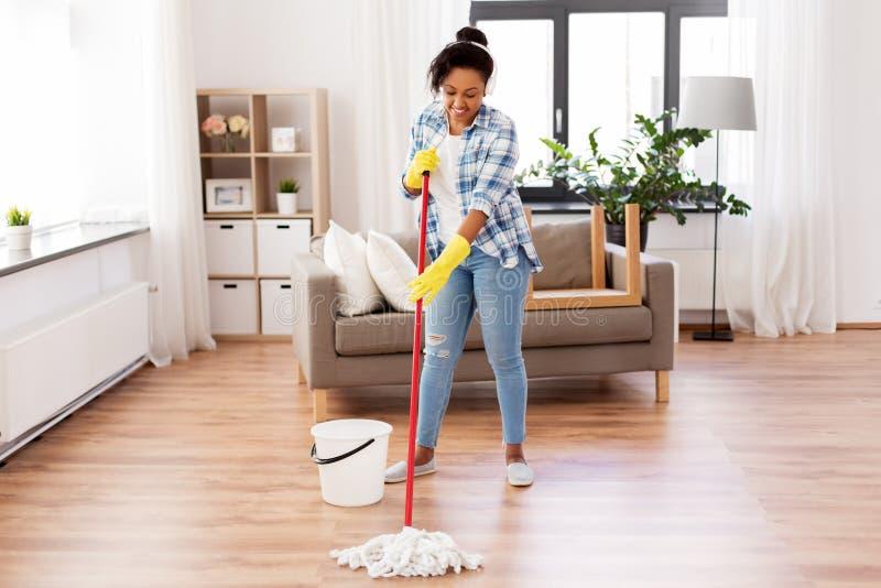 Piso africano de la limpieza de la mujer o del ama de casa en casa imagen de archivo libre de regalías