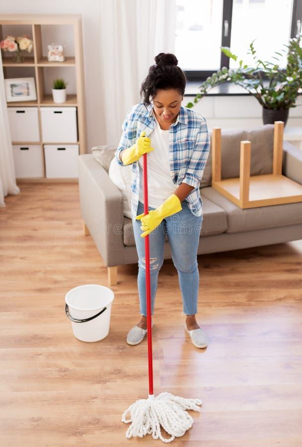 Piso africano de la limpieza de la mujer o del ama de casa en casa imagenes de archivo