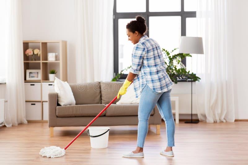 Piso africano de la limpieza de la mujer o del ama de casa en casa fotografía de archivo libre de regalías