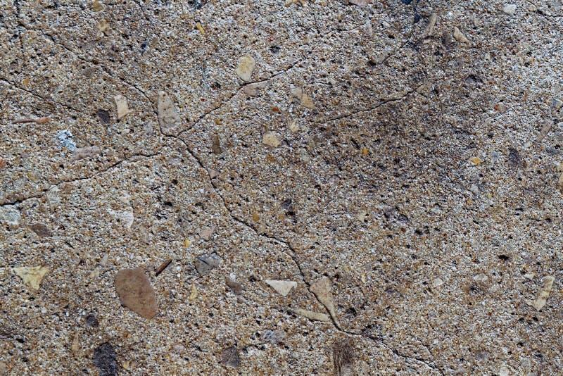 Piso concreto agrietado con cierre del interior de las rocas para arriba imagen de archivo