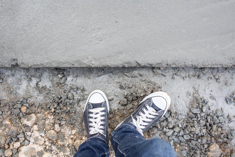 Piso concreto mojado del cemento de la visión superior con la pierna y las zapatillas de deporte del hombre foto de archivo