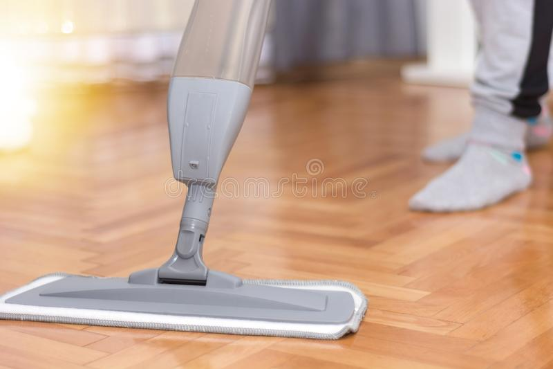 Piso de entarimado de limpieza de la mujer en casa que lava una fregona fotografía de archivo libre de regalías