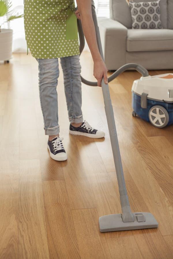 Piso de la limpieza de la mujer con un aspirador en sitio fotos de archivo