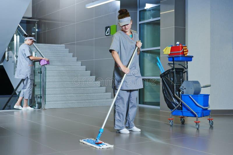 Piso de la limpieza del trabajador con la máquina imagenes de archivo