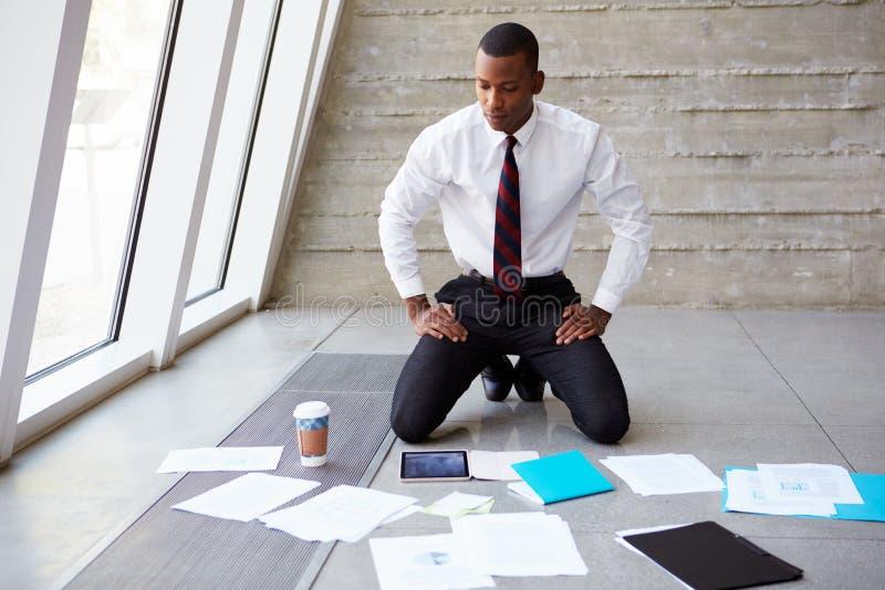 Piso de Laying Documents On del hombre de negocios para planear proyecto imágenes de archivo libres de regalías