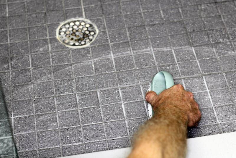 Piso de limpieza de la ducha de la mano masculina imagen de archivo libre de regalías