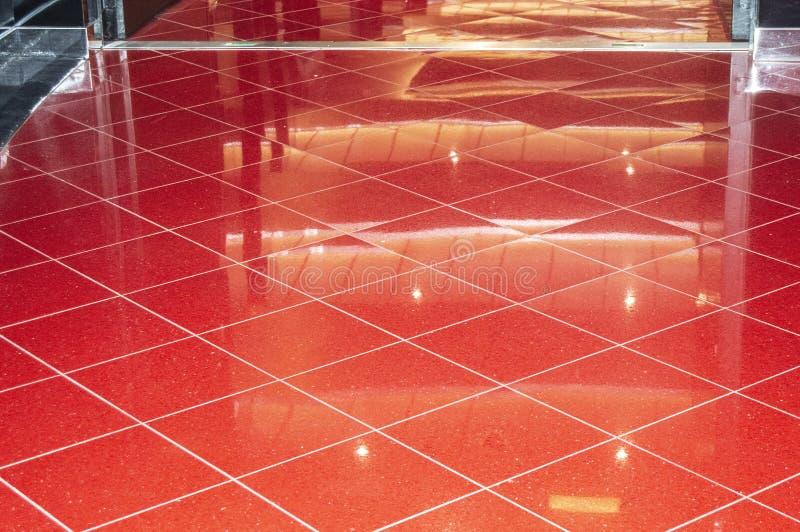Piso de mármol rojo brillante en el pasillo de lujo de la oficina o del hotel, baldosas con las reflexiones para el fondo imágenes de archivo libres de regalías