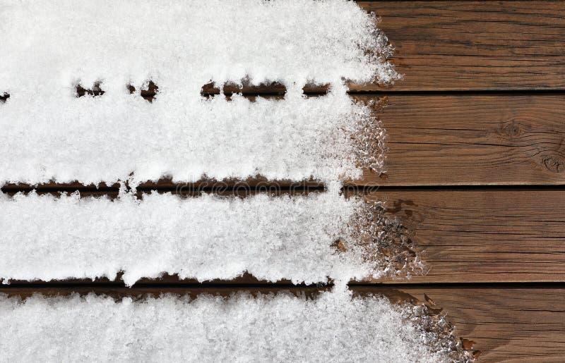 Piso de madera cubierto por la nieve que derrite en la luz del sol Fondo con el espacio de la copia imagen de archivo libre de regalías