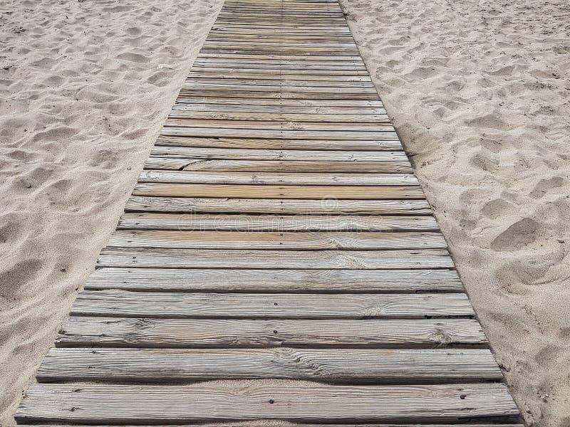 Piso de madera en la playa arenosa de oro fotos de archivo