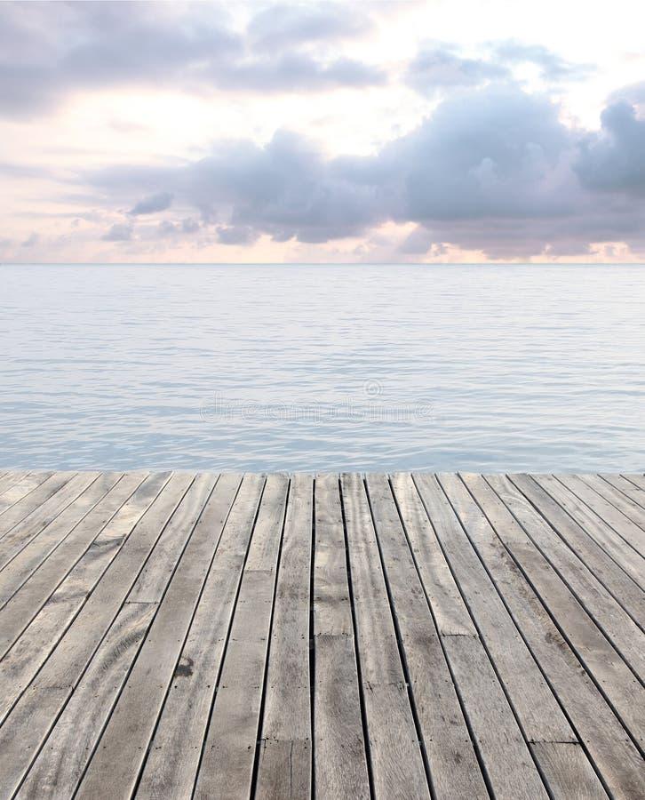 Piso de madera y mar azul con las ondas y el cielo nublado fotografía de archivo libre de regalías