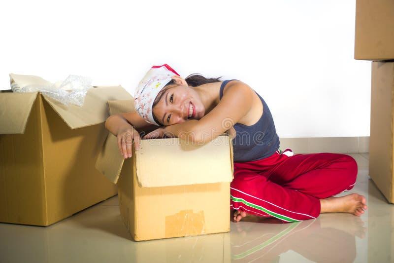 Piso emocionado joven de la sala de estar de la mujer coreana asiática hermosa y feliz en casa que desempaqueta pertenencia de la imagenes de archivo