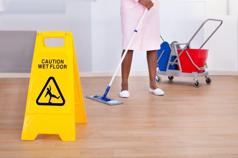 Piso femenino de la limpieza del ama de casa en hotel foto de archivo libre de regalías