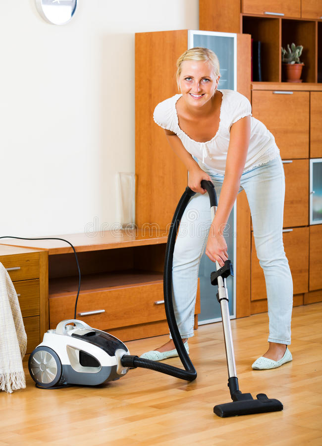 Piso y muebles que limpian con la aspiradora del ama de casa imagen de archivo libre de regalías