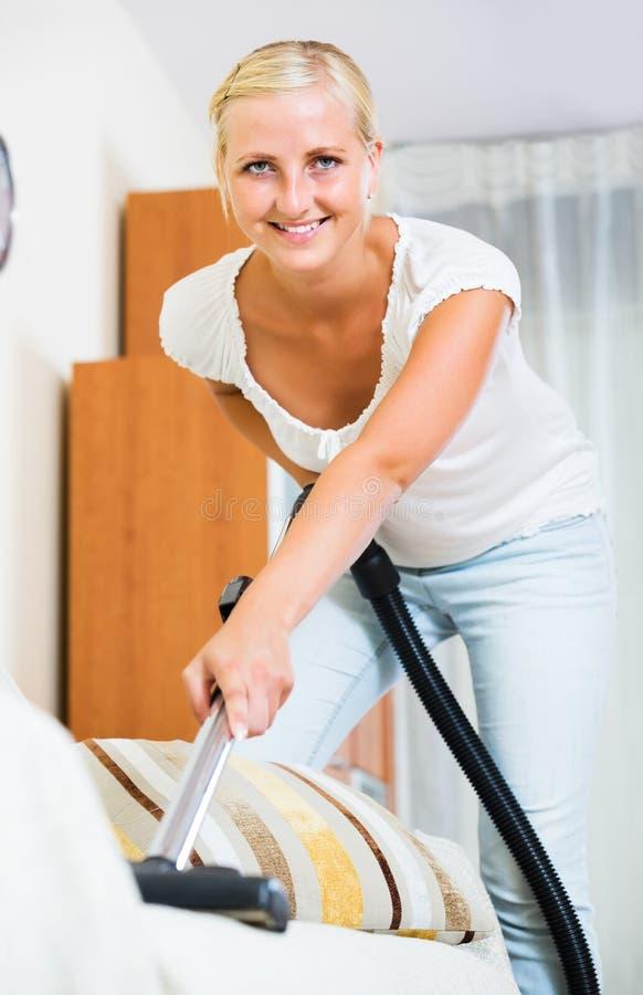 Piso y muebles que limpian con la aspiradora del ama de casa imagenes de archivo