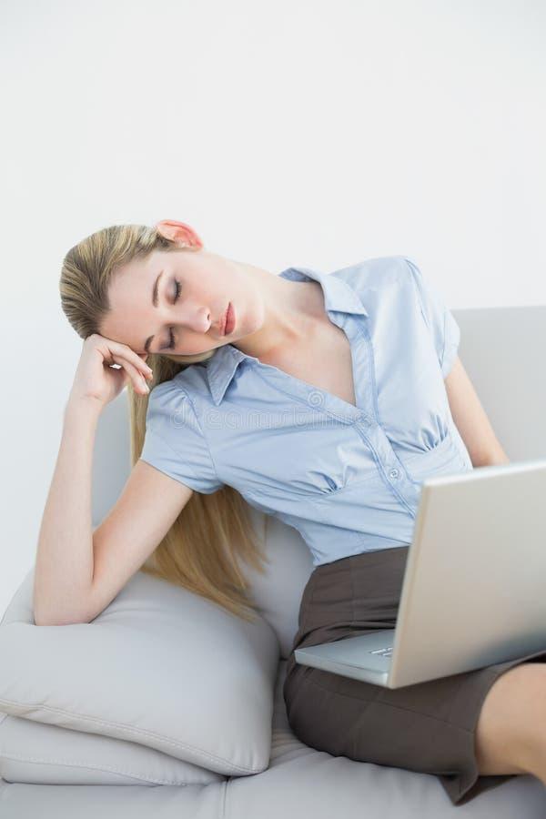 Pisolino stanco della donna di affari che si siede sul suo strato fotografia stock libera da diritti
