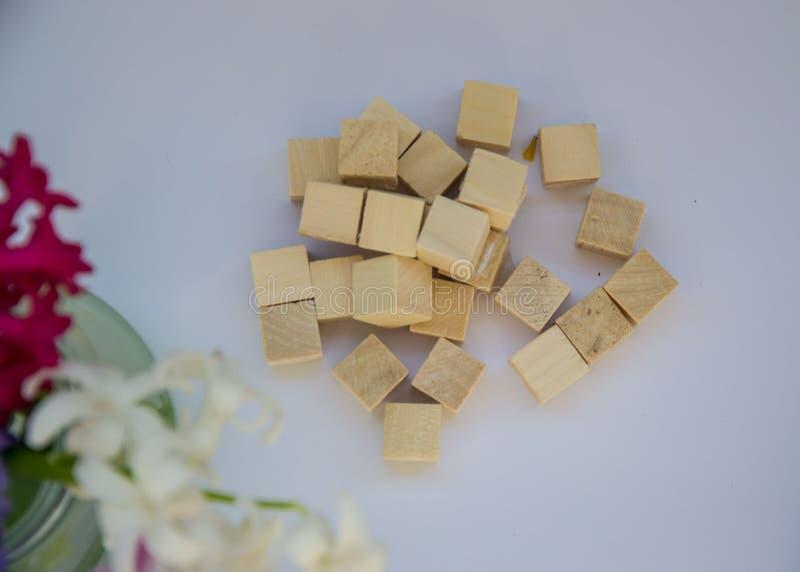 Pisos de madera sobre fondo violeta pálido, pequeños cubos de madera que forman un corazón imagen de archivo