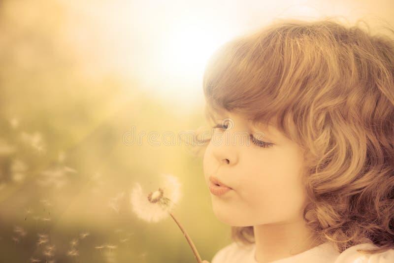 Pissenlit de soufflement d'enfant heureux photo stock