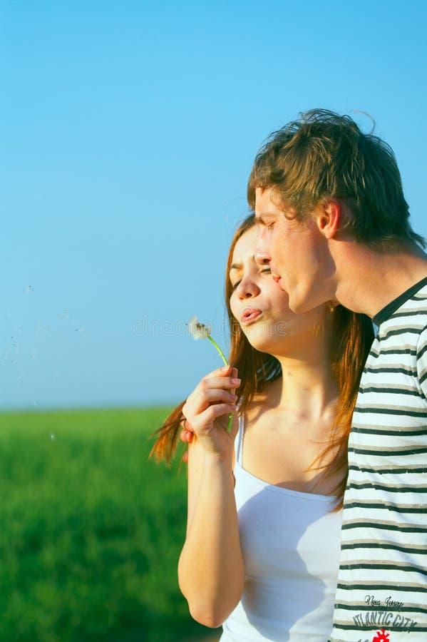Pissenlit de soufflement de jeunes couples images stock