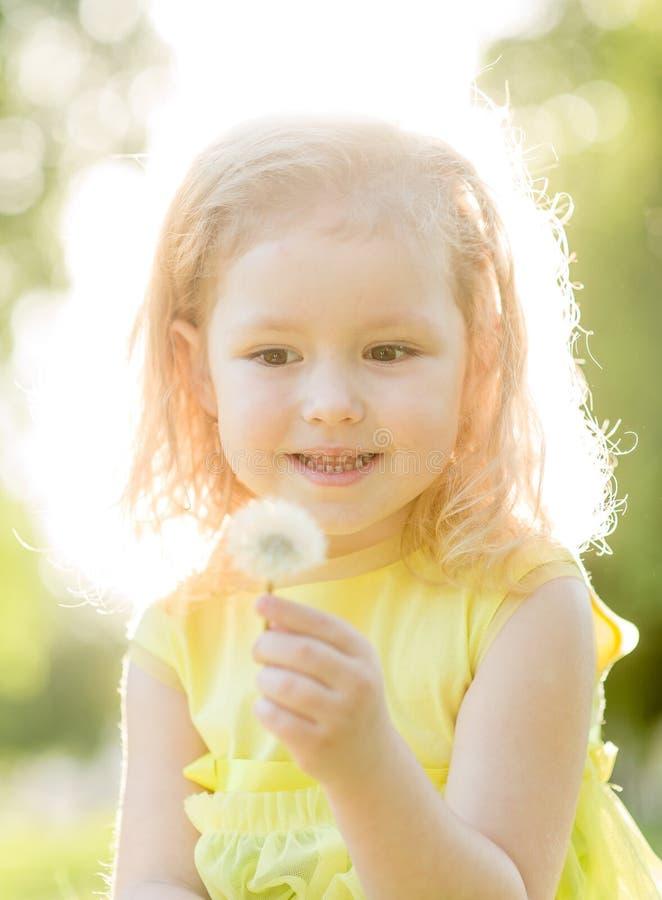 Pissenlit de soufflement de petite fille bouclée photographie stock