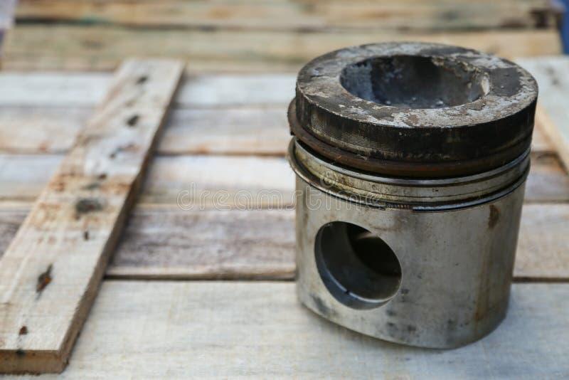 Pistão do motor no fundo de madeira, indústria das peças de automóvel e fundo das peças sobresselentes, dano do pistão em trabalh foto de stock royalty free