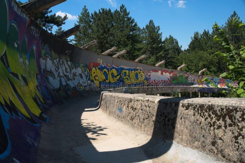 Pista abandonada del trineo de los Juegos Olímpicos 1984 de Sarajevo con la pintada que es dibujada sobre imagen de archivo