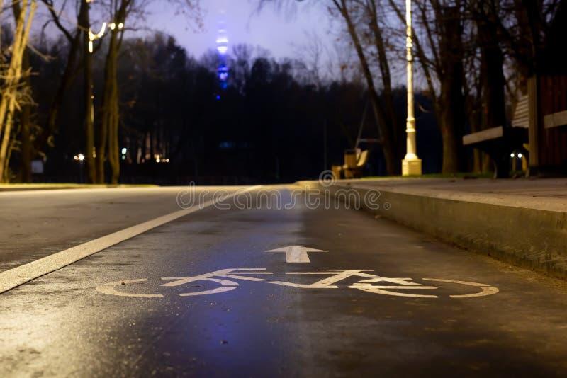 Pista ciclabile del segno Alla notte nel parco questo modo alla vostra salute I fari splendono verso I fari splendono verso Mette immagine stock libera da diritti