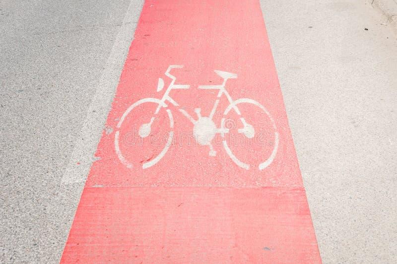 Pista da bicicleta pintada no vermelho como o cuidado na estrada asfaltada com sinal ou símbolo da bicicleta imagem de stock royalty free