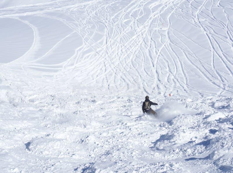 Pista da borla com o snowboarder freerider que esquia para baixo em inclinações cobertos de neve da parte superior da montanha de imagem de stock