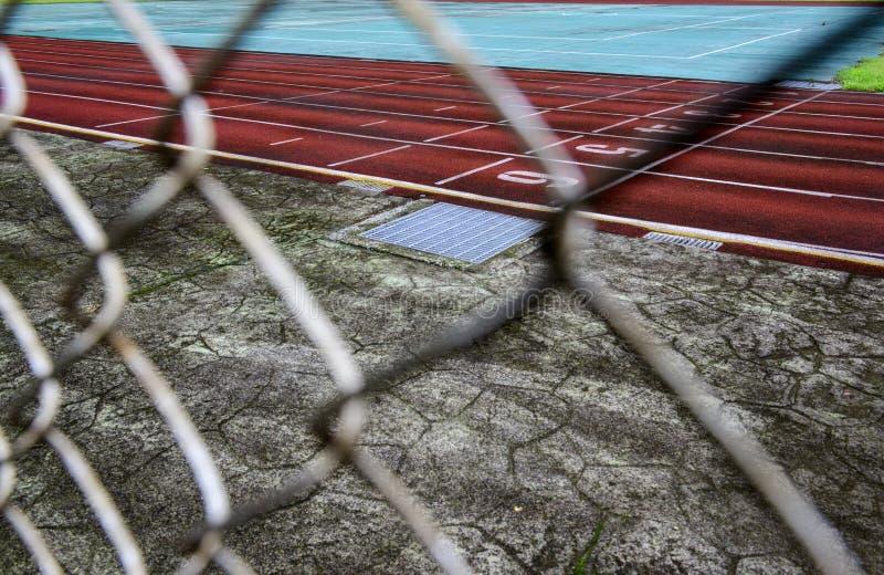 Pista de atletismo através da cerca de fio fotografia de stock royalty free