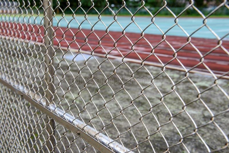Pista de atletismo através da cerca de fio fotos de stock