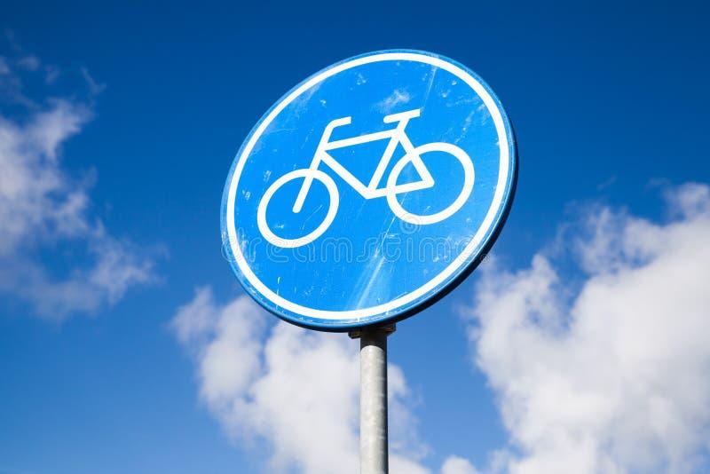 A pista de bicicleta, estrada azul redonda assina sobre o céu nebuloso imagens de stock royalty free