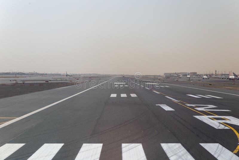 Pista de decolagem do aeroporto de Dubai e aviões estacionados dos emirados imagem de stock royalty free