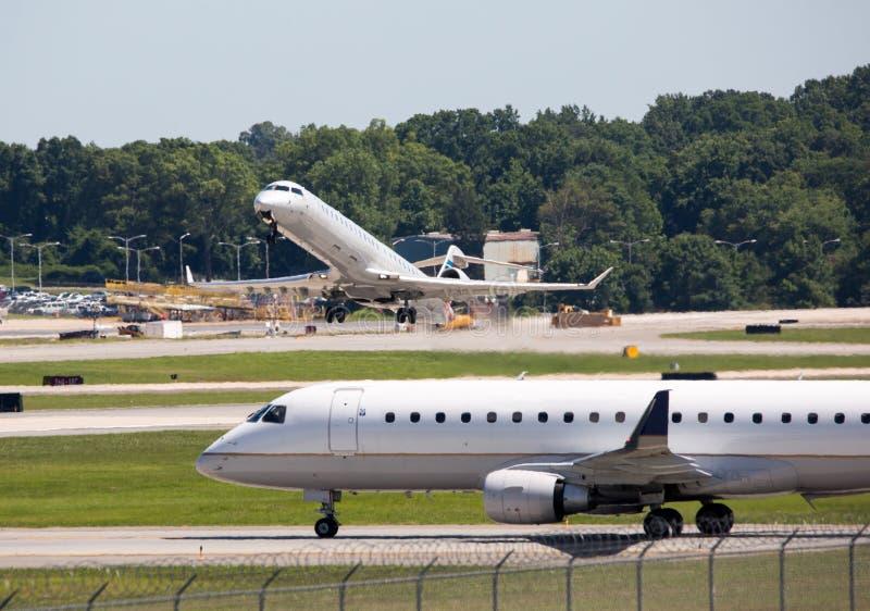 Pista de decolagem ocupada do aeroporto com os dois aviões de passageiros comerciais foto de stock royalty free