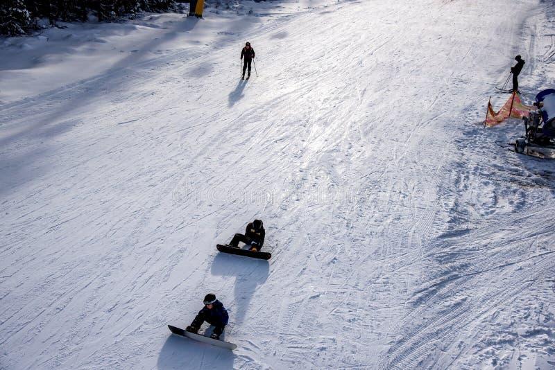 Pista de esquí, gente esquiando por la colina, vista de las montañas fotografía de archivo