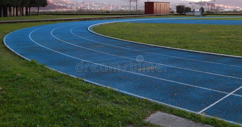 Pista de funcionamiento al aire libre en azul con las líneas blancas fotografía de archivo