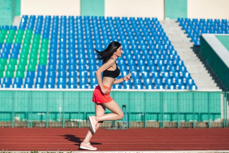 Pista de funcionamiento de la muchacha en estadio Vista lateral real de la mujer joven en pantalones cortos rosados y camisetas s imagen de archivo