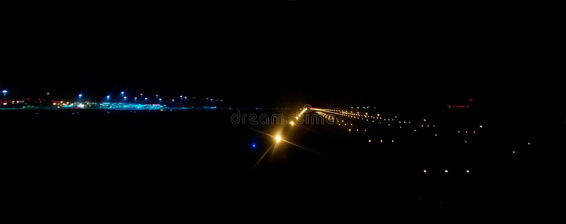 Pista del aeropuerto iluminada por las luces de aterrizaje brillantes en la noche foto de archivo