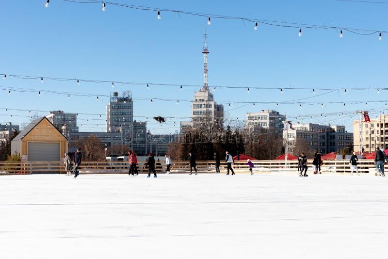 Pista di pattinaggio sul ghiaccio all'aperto al quadrato centrale la gente fa scorrere e si diverte città di Harkìv fotografia stock libera da diritti