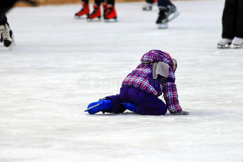 Pista do patim das crianças s Um rapaz pequeno patina e cai no gelo Esporte ativo da família, feriados de inverno e a estação fri fotos de stock