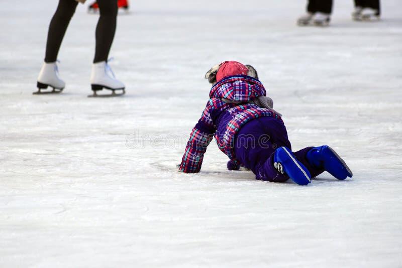 Pista do patim das crianças s Um rapaz pequeno patina e cai no gelo no esporte ativo da família do inverno durante os feriados de imagens de stock