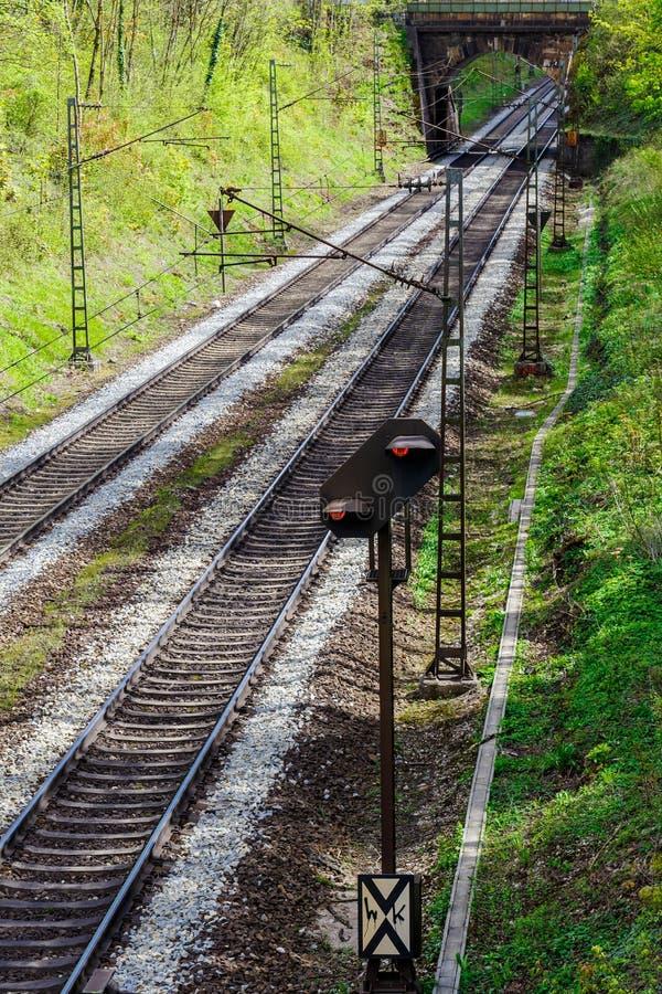 Pista ferroviaria que desaparece debajo de un pequeño puente imagen de archivo libre de regalías