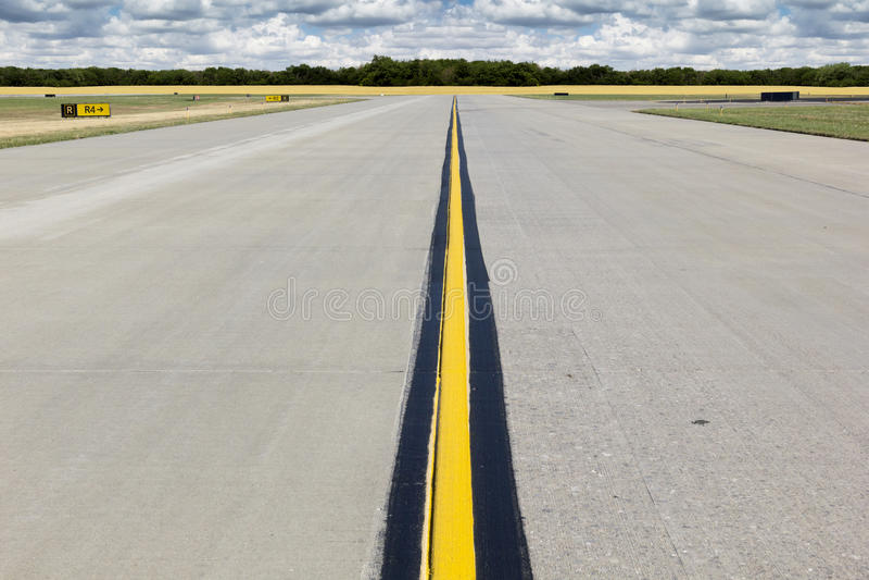 Pista rurale dell'aeroporto con la linea gialla luminosa ed il Wheatfield dorato fotografia stock