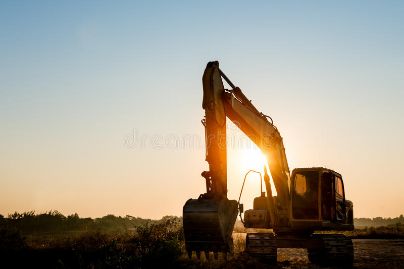 Pista-tipo máquina del excavador del cargador en fondo de la puesta del sol foto de archivo libre de regalías