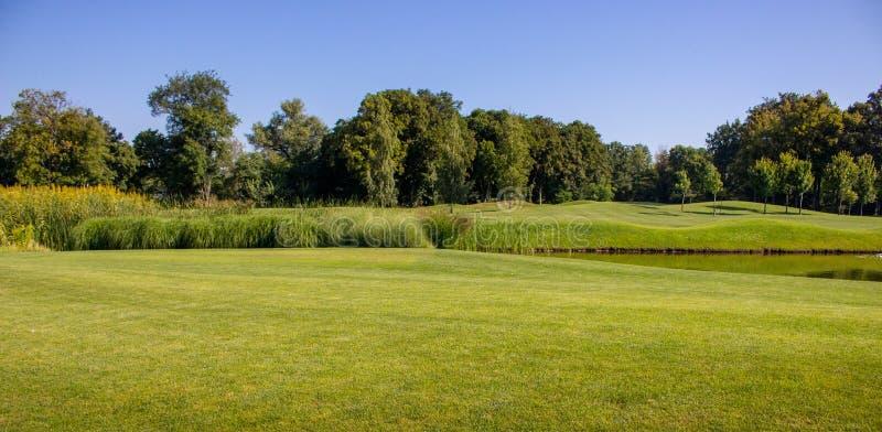 Pista verde bonita do verão com lagoa e árvores contra o céu azul claro Mola e paisagem do parque do verão Campo do golfe com lag fotos de stock royalty free