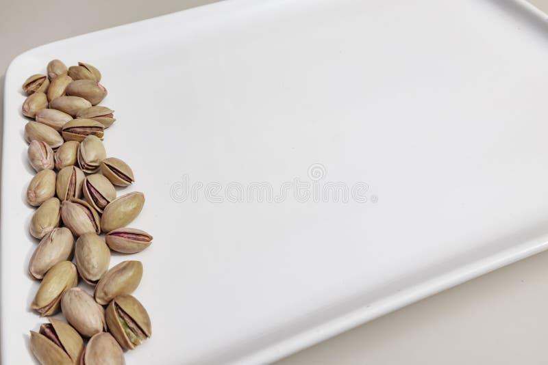 Pistaches écossées dans le plat blanc image stock